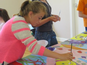 Young girl painting a mural